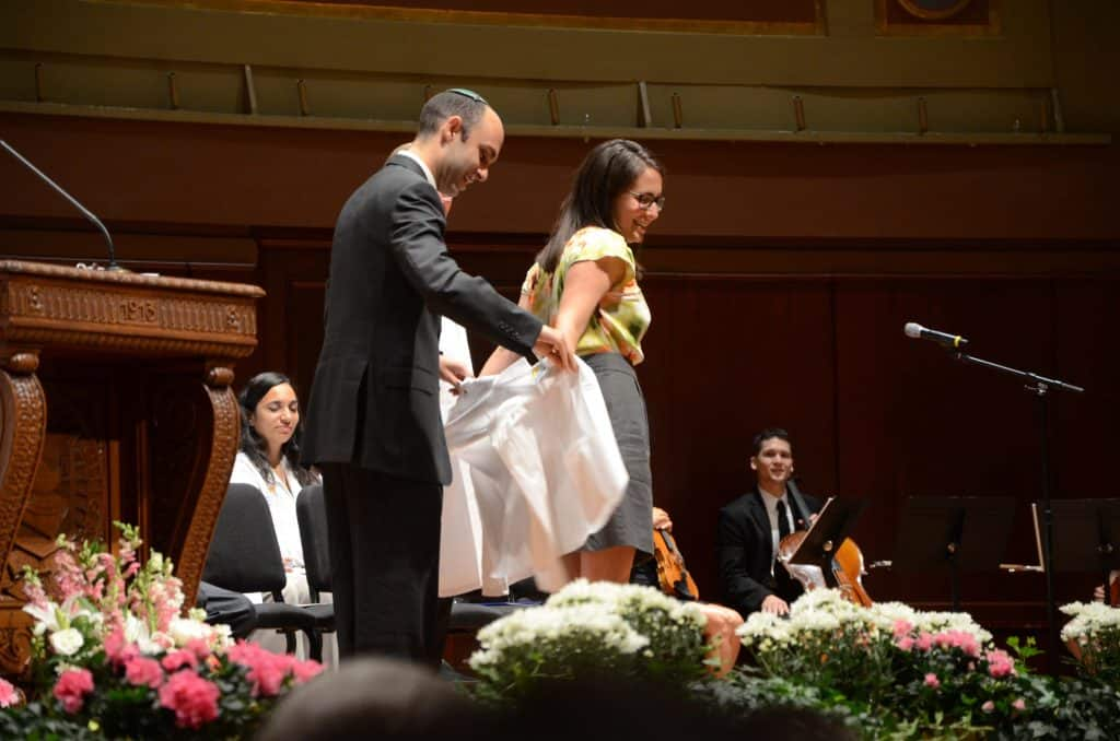 Dr. Sarah Platt receiving her White Coat from her brother, also a physician.